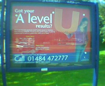 The poster reads 'Just got your A-Level results', next to which is a girl holding a giant U.